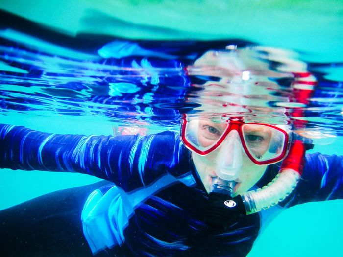 Close-Up Of Woman Wearing Snorkel While Swimming In Sea