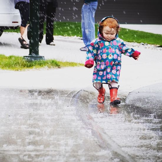 Redhead in the rain Wellington Boots Rainy Days Childhood Child Real People Leisure Activity Full Length Lifestyles Day One Person Women Girls Motion Casual Clothing Females Innocence Warm Clothing