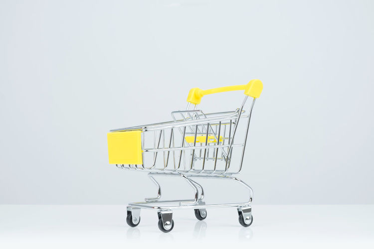 Side view of shopping cart on white Background. Background Basket Business Buy Cargo Container Carrying Cart Chrome Clipping Path Commerce Consumer Consumerism Customer  Customized E-commerce Empty Equipment Finance Food Groceries Grocery Home Finances Isolated Market Marketing Mesh Metal Modern Object Purchase Push Cart Retail  Sale Selling Shop Shopping Cart Shopping Mall Store Supermarket Trade Trolley Wheel White Yellow Yellow Background