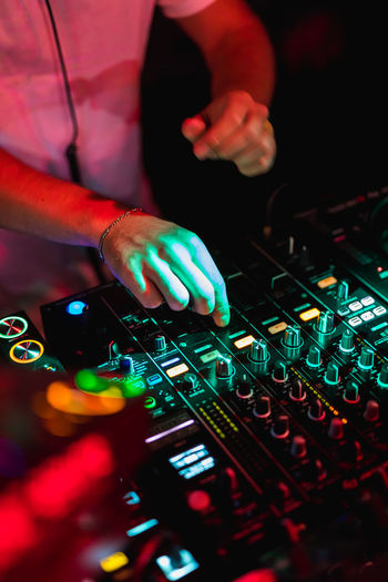 Midsection of dj playing music with sound mixer