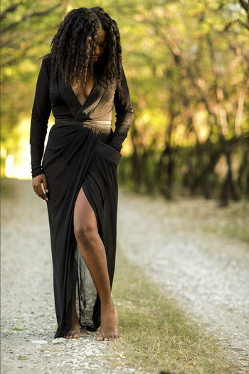 Full length of woman standing on dirt road