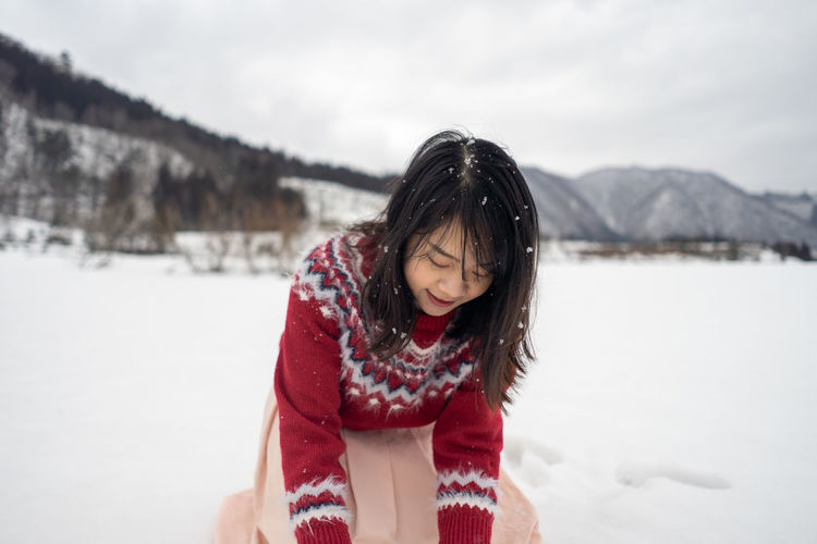 Woman playing with snow during winter