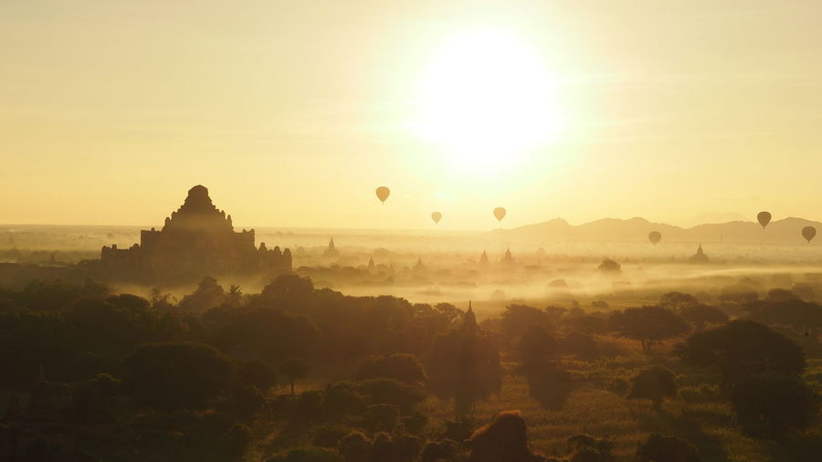Hot air balloons over silhouette temples against sky during sunrise
