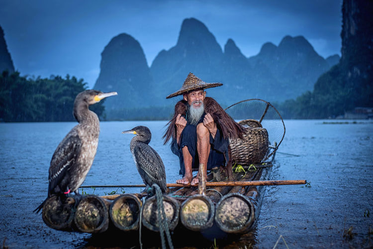 Man with birds sitting on wooden raft in lake