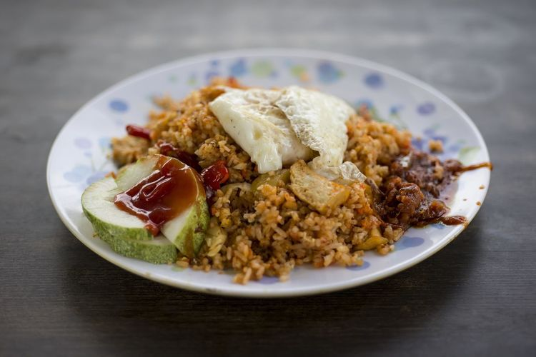 Fried rice with omelet in plate on table