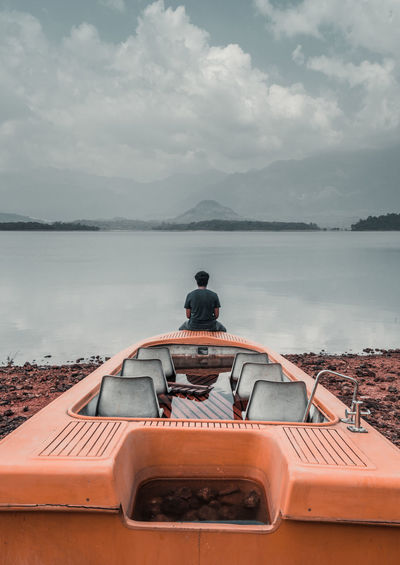 Rear View Of Man Sitting On Boat By Lake Against Cloudy Sky