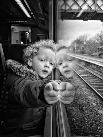 Portrait Of Cute Girl Pointing While Leaning On Window In Train