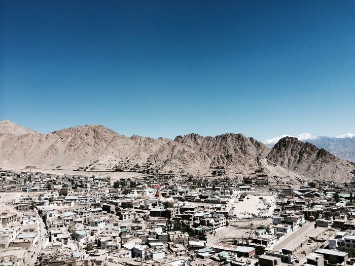 High Angle View Of Town And Mountains Against Clear Blue Sky