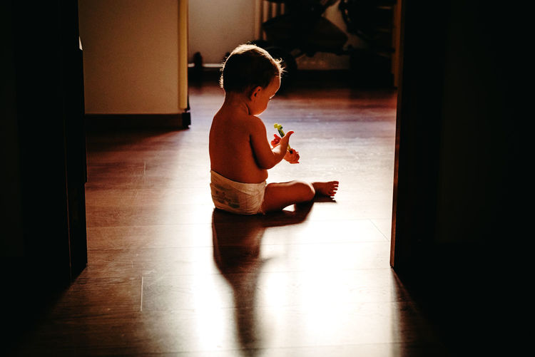 Cute baby girl holding toothbrush while sitting on hardwood floor