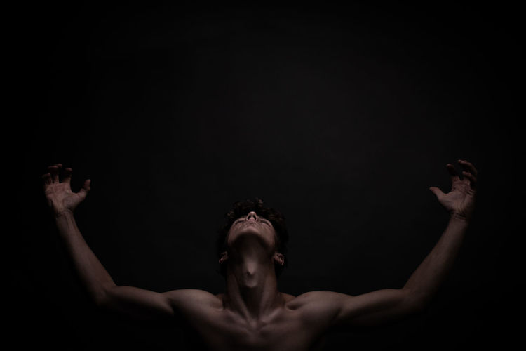 Portrait of shirtless man against black background looking in the sky to the light