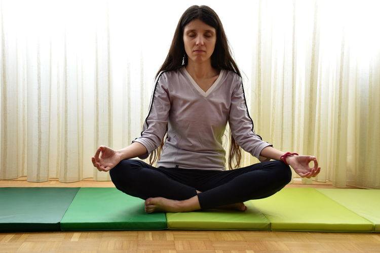 Woman barefoot Cross-legged Curtain Exercising Front View Full Length Healthy Lifestyle Indoors  Lifestyles Long Hair One Person Pad Real People Relaxation Relaxation Exercise Sitting Sports Clothing Yoga Young Adult Zen-like