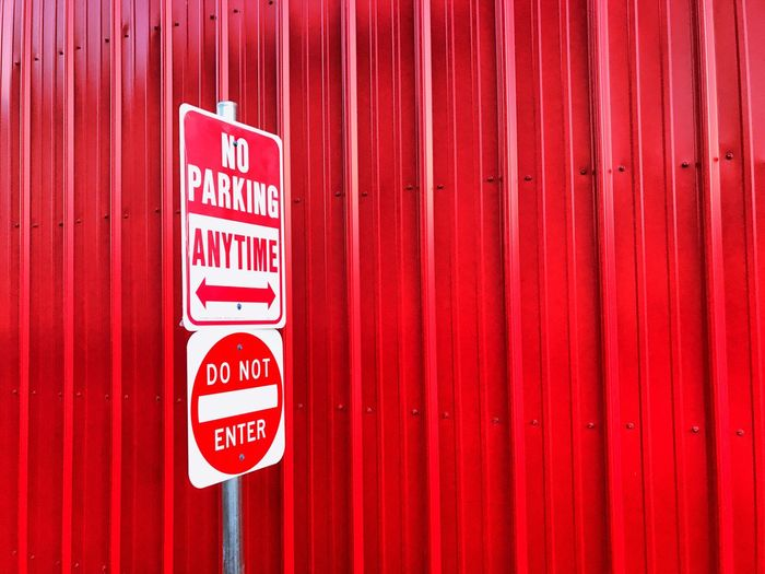 Close-up of no parking sign on red wall