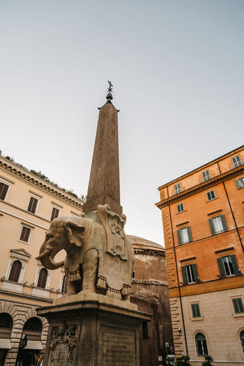 Obelisk in the Square of Minerva in Rome a sunny day of summer with Pantheon on background Minerva Obelisk Square Architectural Column Architecture Building Exterior Built Structure City Clear Sky Clock Tower Day Elephant History Human Representation Low Angle View Male Likeness Monument No People Outdoors Religion Sculpture Sky Spirituality Statue Travel Destinations