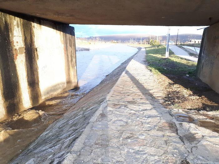 Walkway in water against sky
