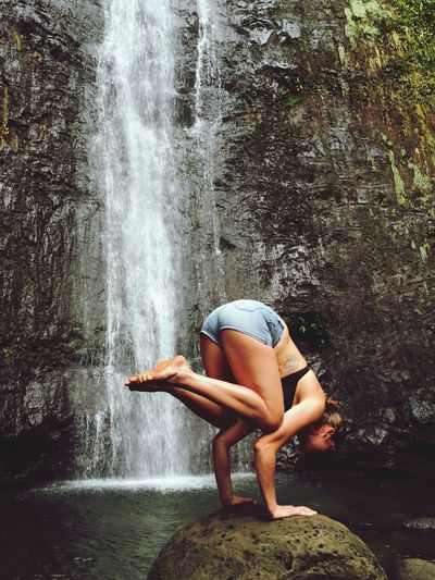 Woman doing handstand against waterfall