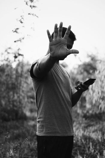 Midsection of man with arms raised standing on field