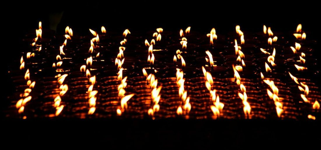 Lighened earthen lamps Black Background In A Row Event Nature Candle Celebration Large Group Of Objects Fire - Natural Phenomenon Heat - Temperature Flame Religion Close-up Indoors  Illuminated Burning Fire No People Glowing Belief