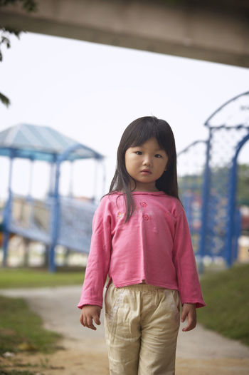 portrait of girl at playground Casual Clothing Child Childhood Day Elementary Age Focus On Foreground Girls Leisure Activity Lifestyles Looking At Camera One Person Outdoors Pink Color Playground Portrait Real People Smiling Standing Walking