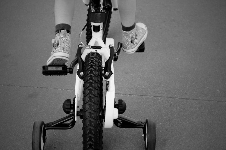 Low section of child riding bicycle on road