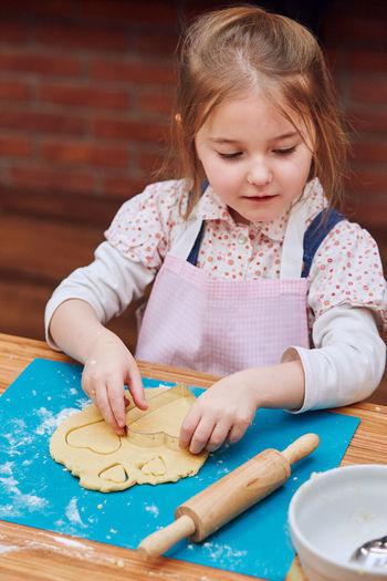 Girl preparing cookie at table
