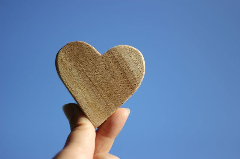 Close-up of hand holding heart shape wood against clear blue sky