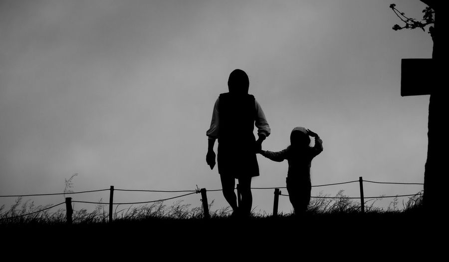 Silhouette couple standing on field against sky