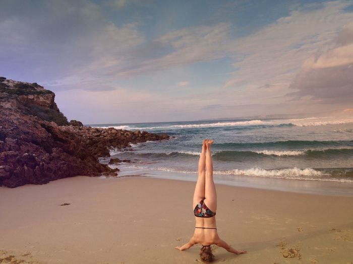 Rear View Of Woman Performing Headstand On Beach
