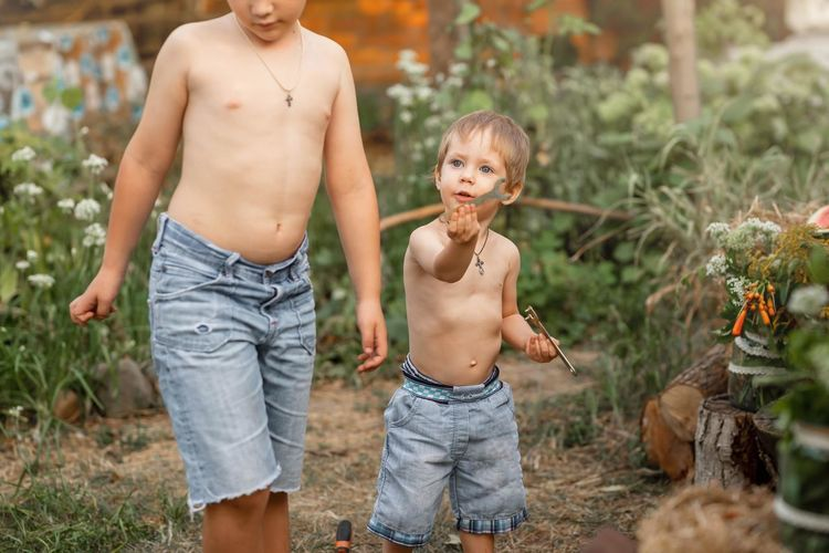 Full length of shirtless boy standing outdoors