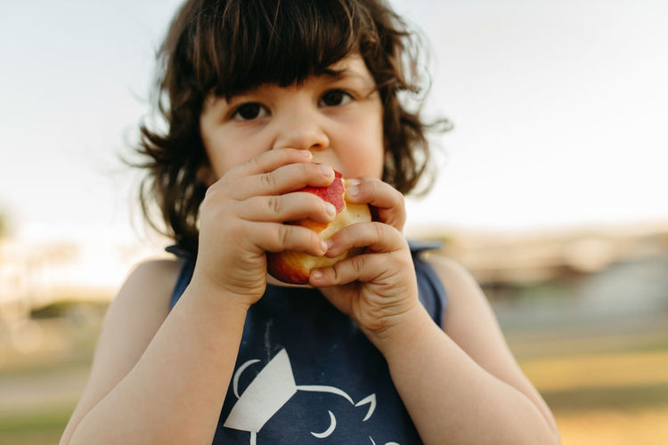 Close-up portrait of girl eating apple outdoors