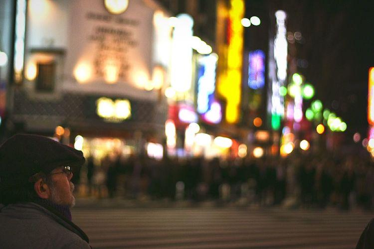 Man at city street against illuminated buildings at night