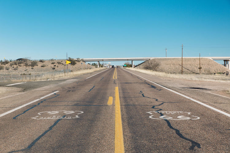 Empty Country Road Passing Through Arid Landscape Against Clear Sky