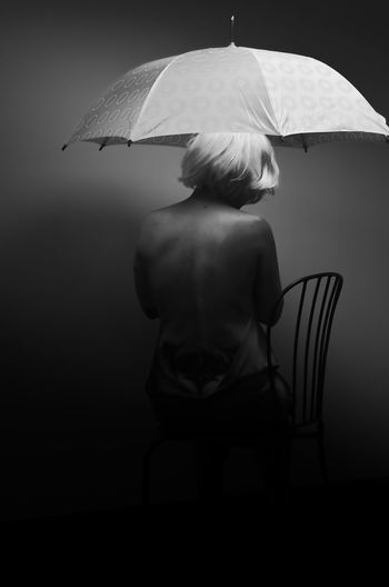 Rear View Of Sensuous Woman With Umbrella Sitting On Chair