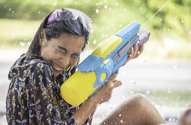 Side view of woman spraying water from gun while sitting outdoors