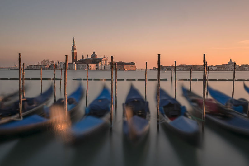 Gondolas moored in canal during sunset