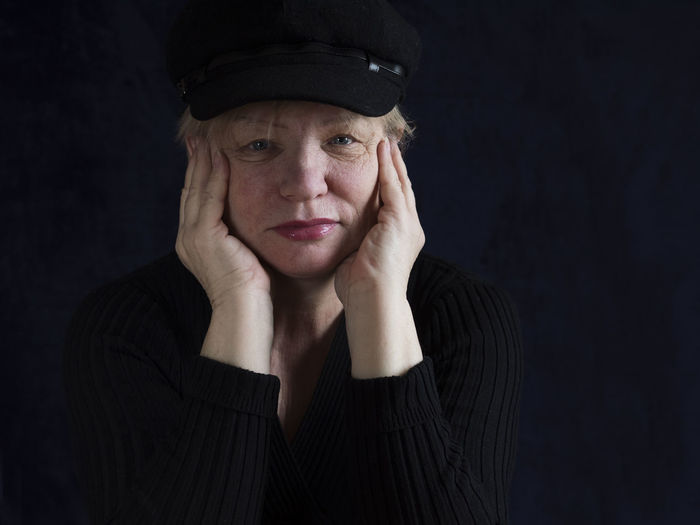Portrait Of Senior Woman Wearing Cap Against Black Background