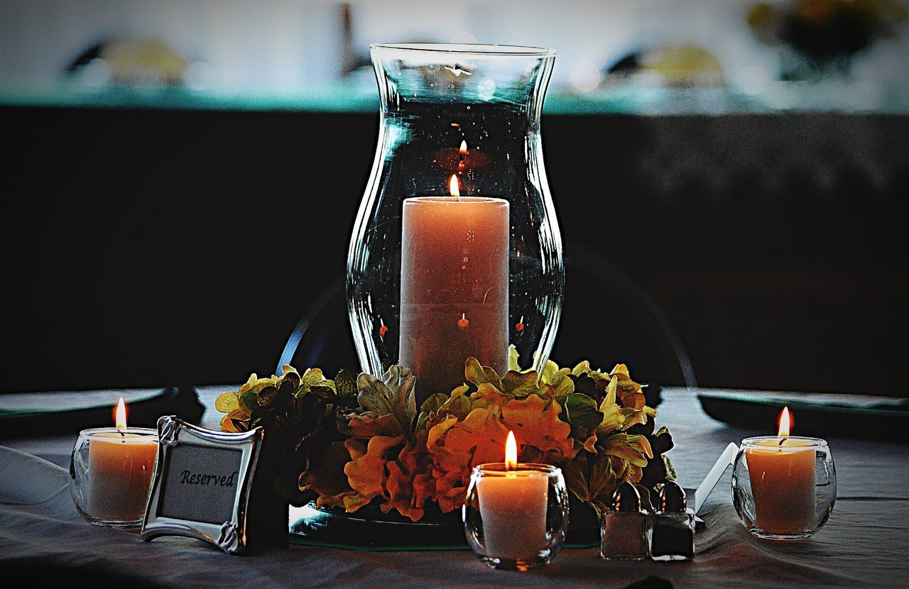 Lit Tea Light Candles And Reserved Sign On Dining Table