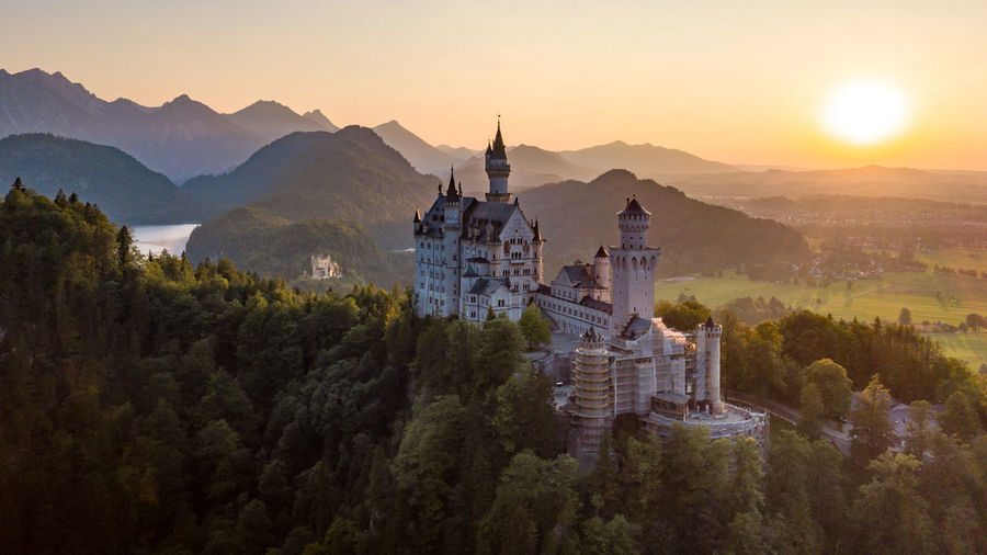 High angle view of castle amidst trees against mountains during sunset