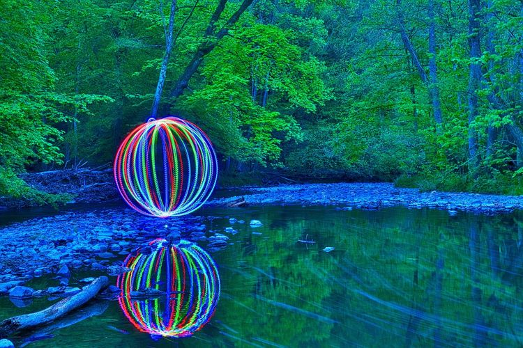 Multi colored light trails over lake in forest