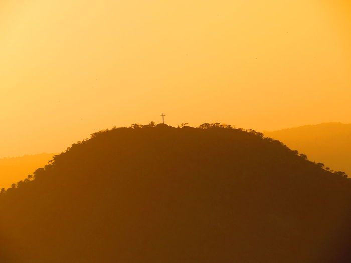 Low angle view of cross on mountain against clear orange sky during sunset