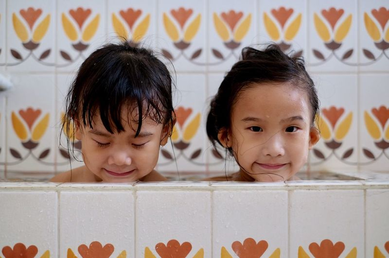 Two Asian little girls are bathing in the tub. Bath Bathtub Shower Tub Bathing Bathroom Childhood Child Girls Portrait Females Boys Offspring Headshot Women Front View Indoors  Males  Togetherness Leisure Activity Real People Emotion Casual Clothing Innocence Sister