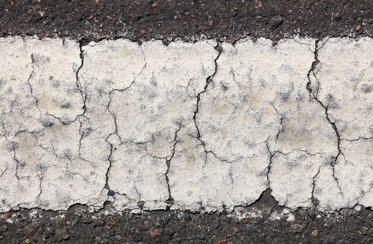 Cracks and breaks in white road surface marking, detailed extreme close up Asphalt Background Beneath Your Feet Break City Close-up Concrete Cracked Detail Directly Above Extreme Footpath Ground High Angle View Paint Road Road Marking Split Street Surface Level Texture Traffic Transportation Urban White The Graphic City Colour Your Horizn
