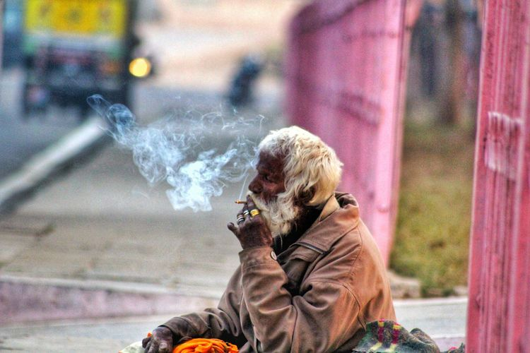 Senior man smoking while sitting on footpath