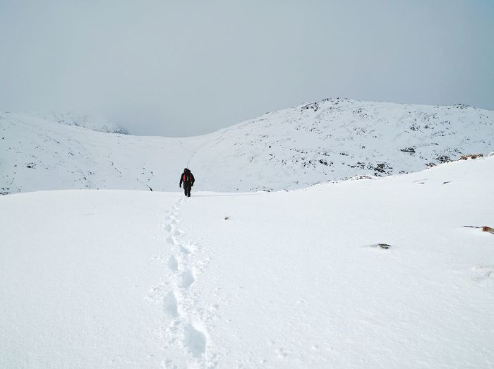 Man on snow covered mountain against sky