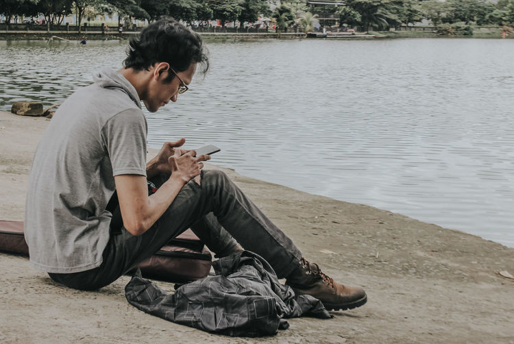 Side view of young man using mobile phone in water