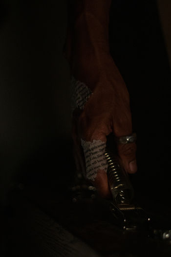 Low section of man holding cigarette against black background