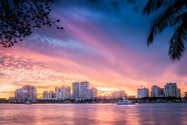 City of West Palm Beach, Florida skyline with waterfront and sunset. City Of West Palm Beach Downtown Skyline West Palm Beach Yachts Yachts At Anchor Architecture Boats Built Structure Coconut Palm Tree Florida Sunset Travel Destinations Urban Skyline Waterfront Waterway