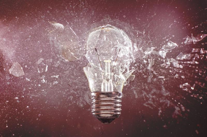Close-up of busting light bulb against black background