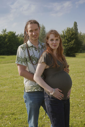 Portrait of man with pregnant wife standing on grassy field against sky