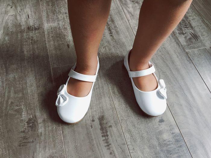 Low Section Of Girl Wearing Shoes On Hardwood Floor