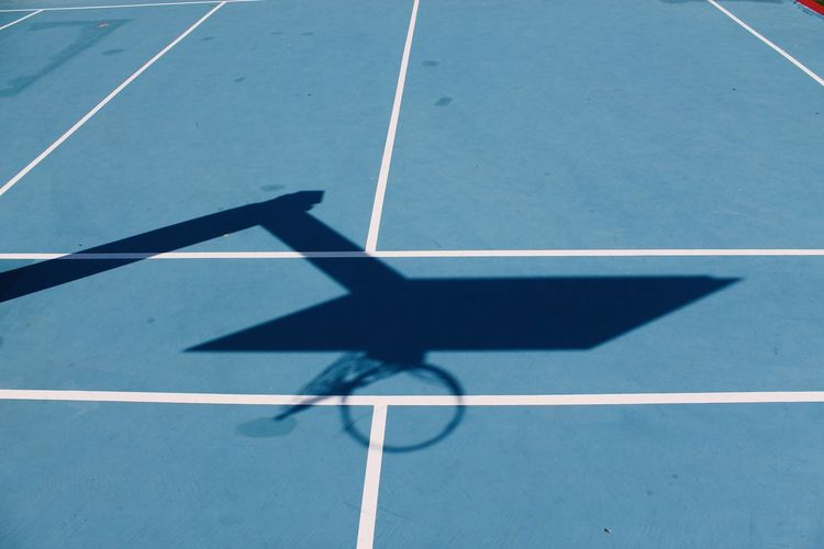 High angle view of basketball hoop shadow pn blue court